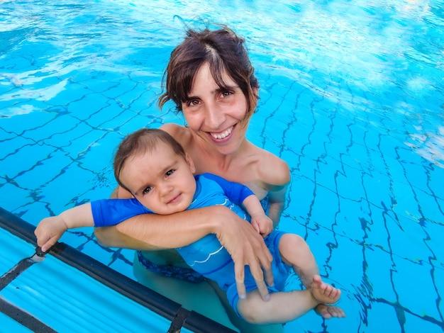 Een blanke moeder met haar baby die voor het eerst in een zwembad baadt
