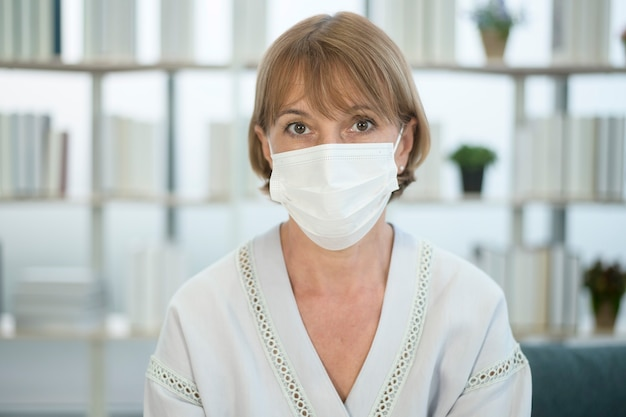 Een blanke senior vrouw die een masker draagt, covid19 pandemisch concept