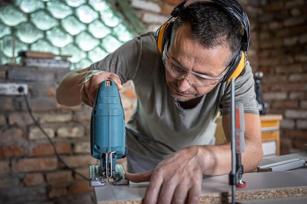 Een blanke timmerman concentreert zich in zijn werkplaats op het zagen van hout met een decoupeerzaag.