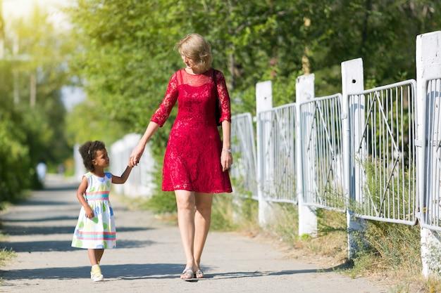 Een blanke vrouw loopt op straat met een zwart meisje.