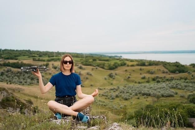 Een blanke vrouw met een drone in haar hand, zittend op een groene rotsachtige heuvel met sky