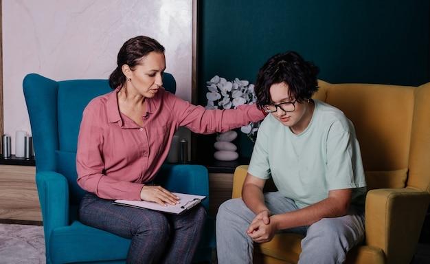Een blanke vrouwelijke psycholoog zit in een fauteuil en raadpleegt een tienermeisje in een fauteuil op kantoor