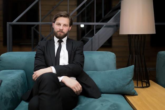 Een blanke zakenman die een pak en stropdas draagt en naar de camera glimlacht terwijl hij praat Premium Foto