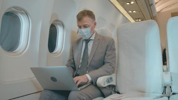 Een blanke zakenman werkt met een laptop in een vliegtuig en draagt tijdens het reizen een beschermend masker tegen covid-19-bescherming
