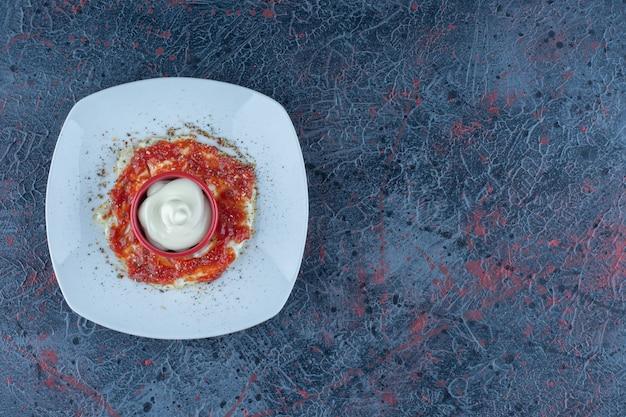 Een blauw bord gebakken ei met kruiden en tomatensaus.