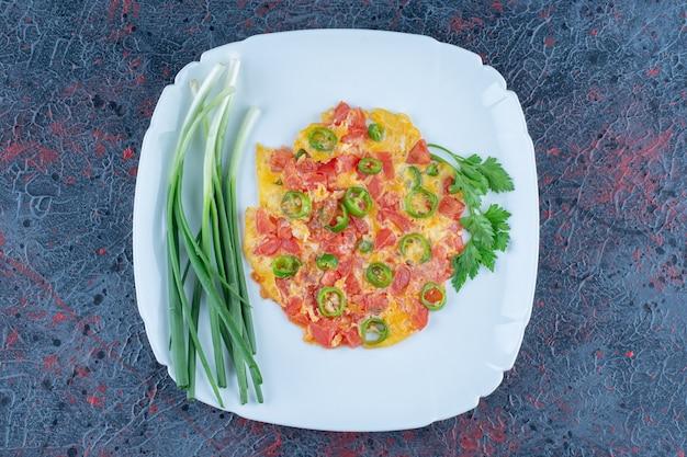 Een blauw bord gebakken eieren met groenten.
