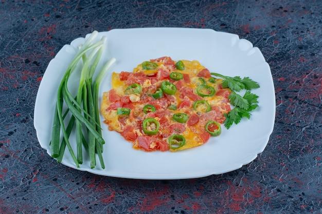 Een blauw bord gebakken eieren met groenten