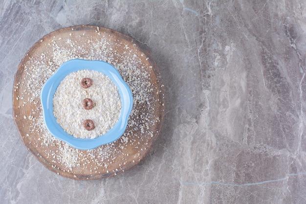 Een blauw bord gezonde havermoutpap met chocoladegranenringen.