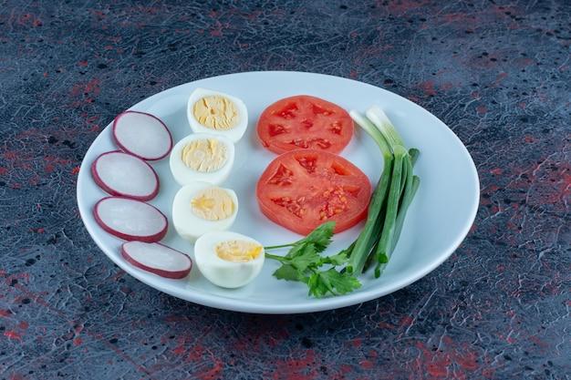 Een blauw bord hardgekookte eieren met groenten
