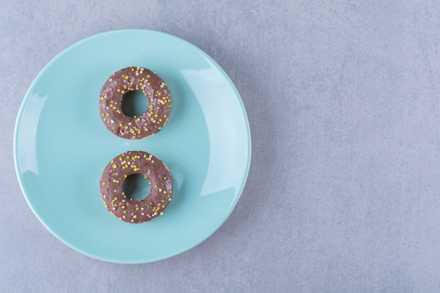 Een blauw bord heerlijke chocolade donuts met kleurrijke hagelslag.
