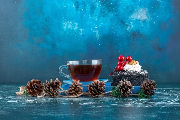 Een blauw bord met een stuk chocoladetaart en een kopje thee. hoge kwaliteit foto