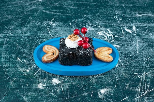 Een blauw bord met een stuk chocoladetaart en koekjes. hoge kwaliteit foto
