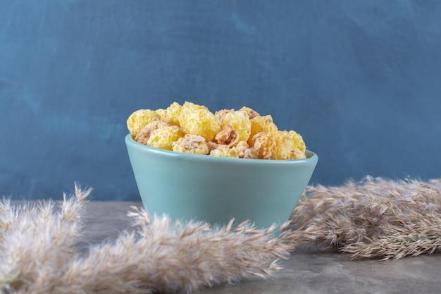 Een blauw bord met gezonde zoete cornflakes op grijze tafel.