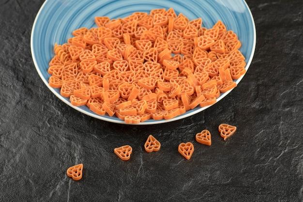 Een blauw bord met rauwe pasta in hartvorm op zwarte tafel