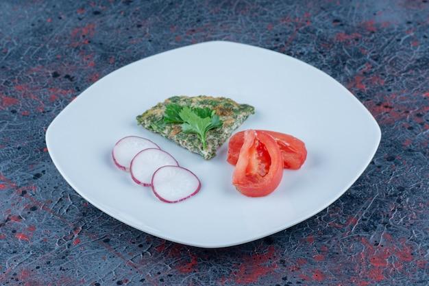 Een blauw bord omelet en gesneden tomaat met gesneden radijs.