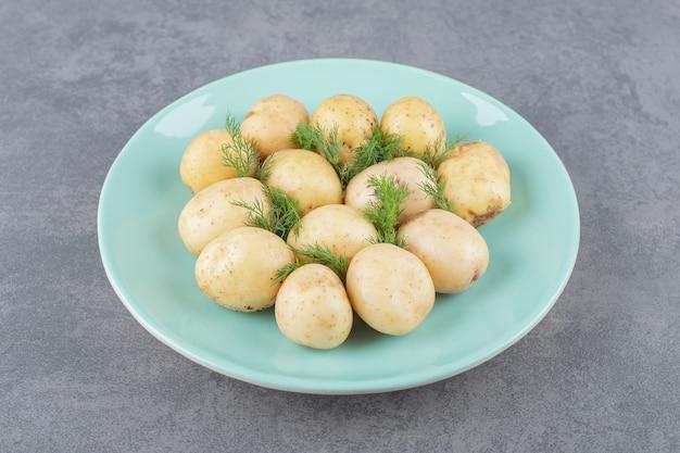 Een blauw bord van gekookte aardappelen met verse dille.