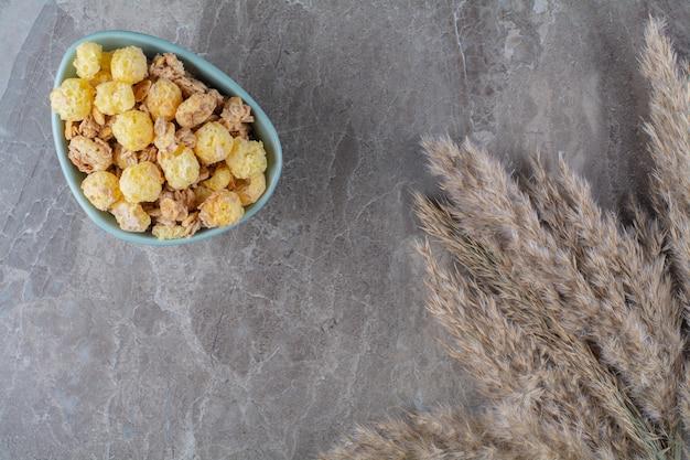 Een blauw bord van gezonde zoete cornflakes op een grijze achtergrond.