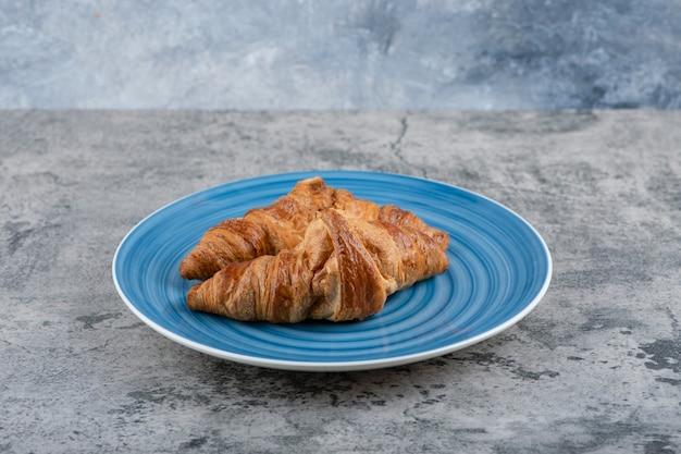 Een blauw bord van twee eenvoudige verse croissants op een stenen tafel.
