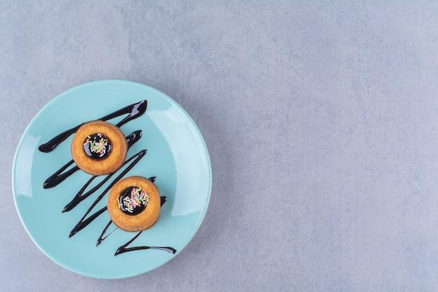 Een blauw bord van twee zoete donuts met kleurrijke hagelslag.