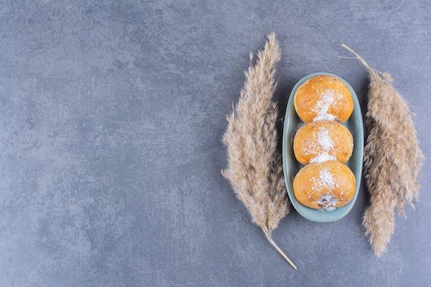 Een blauw bord van zoete cakes met suiker en tarweoren op een steen.