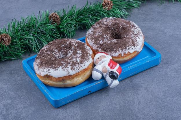 Een blauw bord van zoete chocoladekoekjes met kerststuk speelgoed