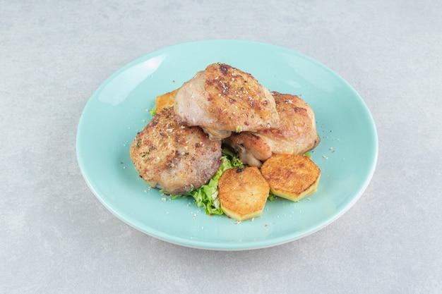 Een blauw bord vlees met gebakken gesneden aardappelen en sla.