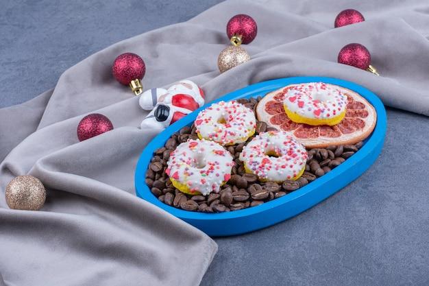 Een blauw bord vol koffiebonen en donuts