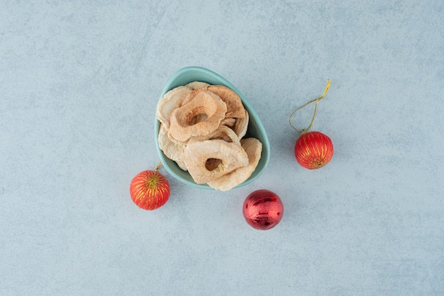Een blauw bord vol met gedroogde gezonde vruchten met rode kerstballen. hoge kwaliteit foto