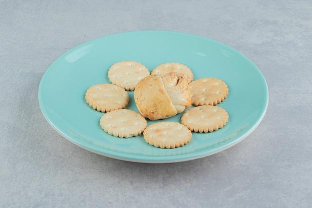 Een blauw bord vol zoete knapperige koekjes met cupcake.