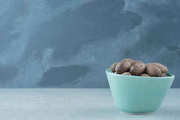 Een blauw bordje vol noten op marmeren achtergrond. hoge kwaliteit foto