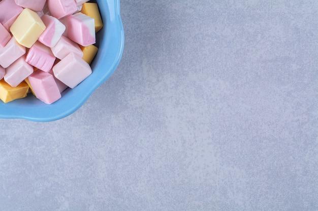 Een blauw diep bord vol kleurrijke zoete zoetwaren pastila