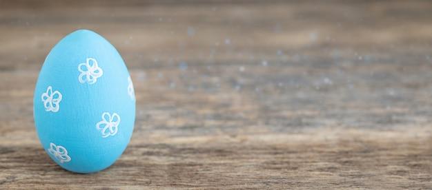 Een blauw geschilderd paasei op houten achtergrond