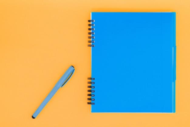 Een blauw notitieboekje met een handvat op de oranje muur. plat lag sjabloon. plaats voor tekst.
