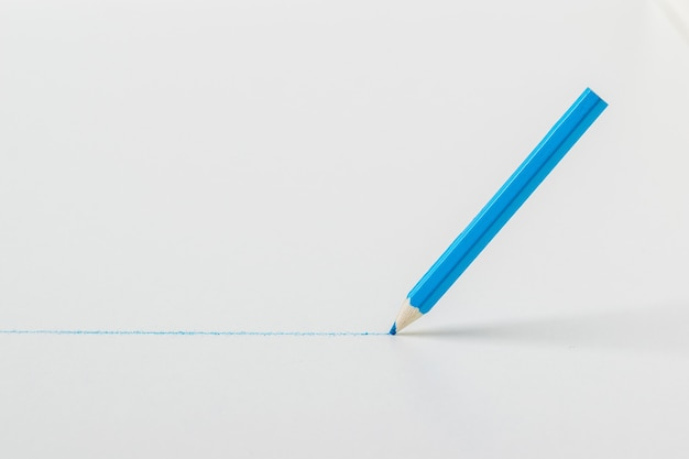 Een blauw potlood tekent een lijn op een witte achtergrond. schrijfwaren en schoolbenodigdheden.