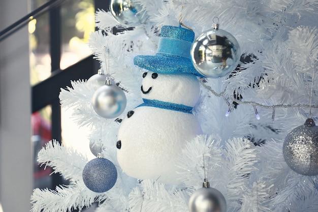 Een blauw sneeuwman speelgoed en veel zilveren ballen hangen aan een witte kerstboom om de woonkamer te verfraaien
