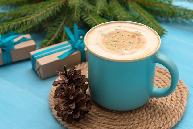 Een blauwe beker met koffie en geschenken op een lichtblauwe houten tafel op kerstavond.