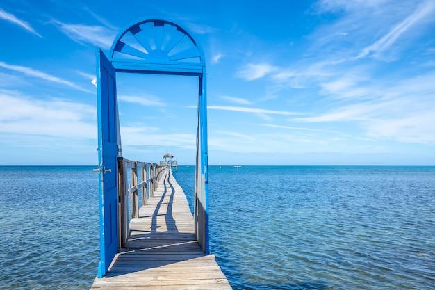 Een blauwe deur op een houten loopbrug op het caribische eiland roatan in honduras