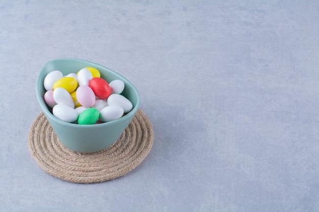 Een blauwe diepe kom vol kleurrijke bonen snoepjes op grijze tafel.