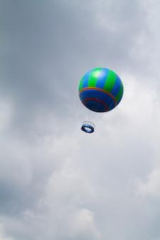 Een blauwe en groene heteluchtballon stijgt op in een onheilspellende grijze bewolkte hemel