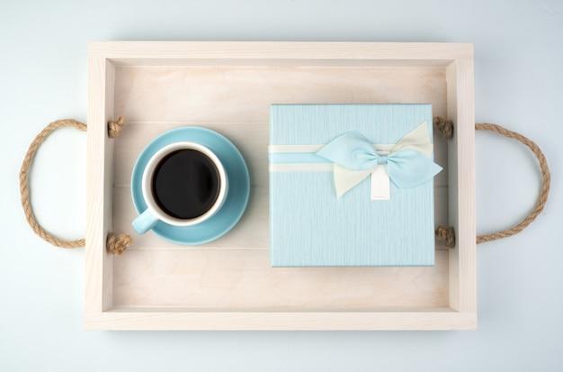 Een blauwe geschenkdoos en een kopje koffie op een wit dienblad