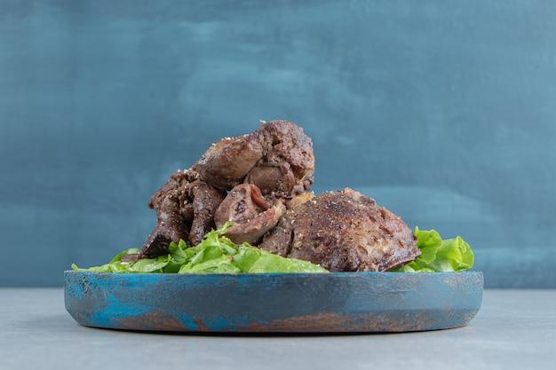 Een blauwe houten plaat van gebakken vlees en gesneden sla.