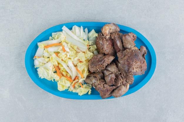 Een blauwe houten plaat van gebakken vlees en groentesalade.