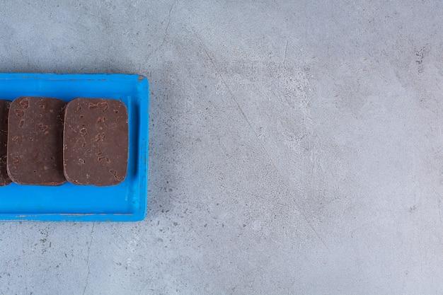 Een blauwe houten plank met chocoladekoekjes op grijs