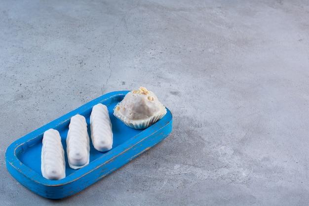 Een blauwe houten plank met zoete witte stokjes en cupcake.