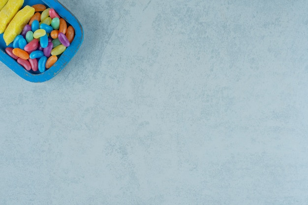 Een blauwe houten plank van banaanvormige kauwsnoepjes met kleurrijke bonensnoepjes