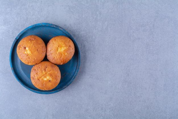 Een blauwe houten plank van drie zoete verse cupcakes.