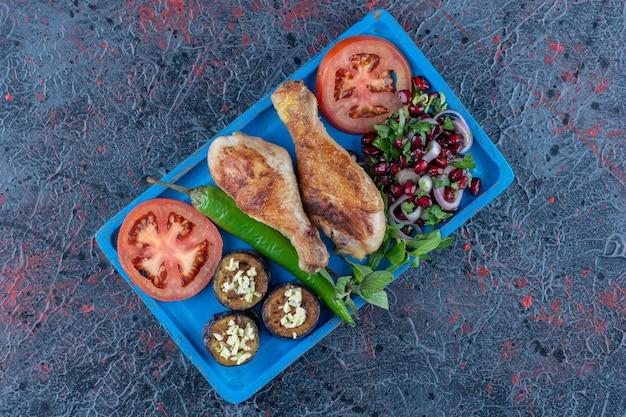 Een blauwe houten plank van gegrild kippenvlees.