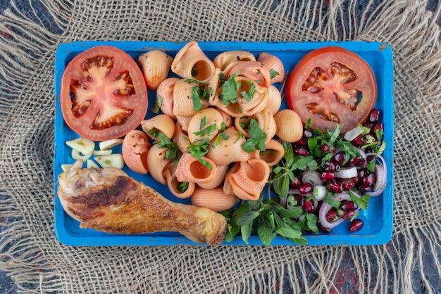 Een blauwe houten plank van kippenbout en macaroni