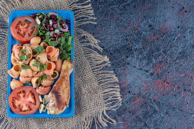 Een blauwe houten plank van kippenpoot en macaroni.