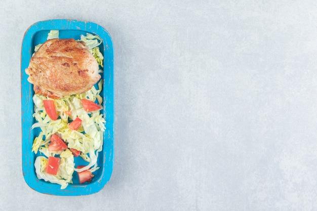 Een blauwe houten plank van kippenvlees met groentesalade.